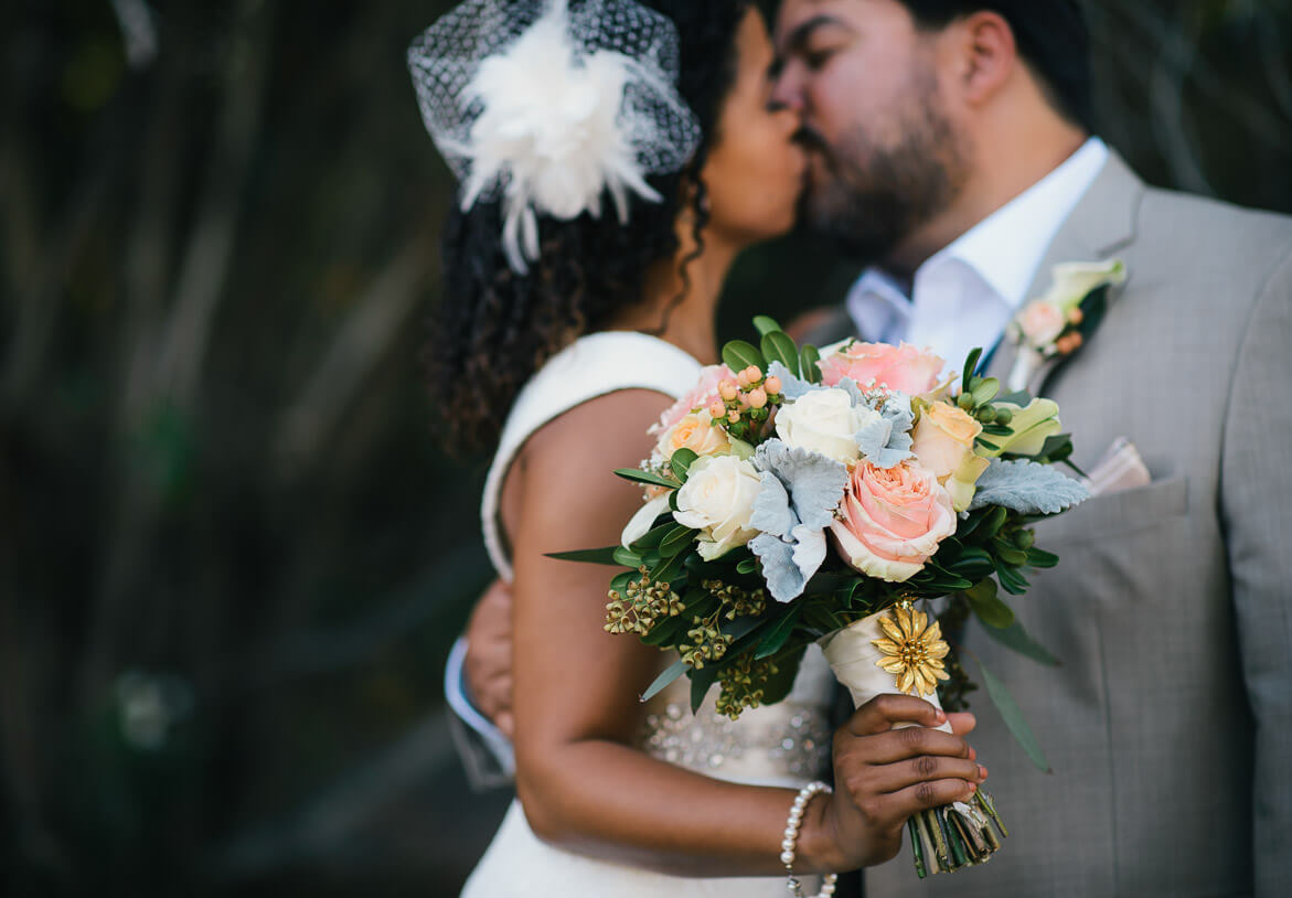 Bride and groom kissing with flowers travel photography wedding